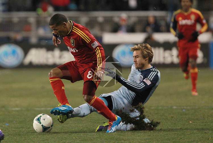 Real Salt Lake forward Jou Plata (8) is challenged by Sporting KC defender Seth Sinovic (15) even through he had fallen while trying to get possession of the ball in the first overtime period. Sporting KC defeated Real Salt Lake in a shootout after the score was tied 1-1 at the end of regulation play in the MLS Cup 2013 championship held at Sporting Park in Kansas City, Kansas on Saturday December 7, 2013.