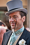 A man in the New York City Easter Parade wearing a gray suit, a top hat, small vintage eye glasses, and a fancy tie
