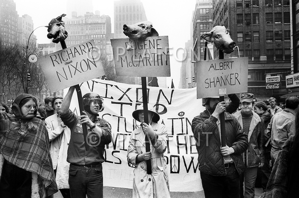 08 Apr 1969 --- Demonstrators in New York City protesting the Vietnam War, which as of this month has claimed more soldiers' lives than that of the entire Korean War. Last month, the United States began secret bombing campaigns of North Vietnamese and Vietcong bases in Cambodia. <br /> New York City, NY. 8 avril 1969. <br /> Les hippies manifestent contre l&rsquo;escalade de la guerre au Vietnam. Nixon est le premier vis&eacute;. De vraies t&ecirc;tes de cochons seront plant&eacute;es sur des piquets. Ce sera la seule fois o&ugrave; je verrai de vraies t&ecirc;tes de cochons utilis&eacute;es pendant des d&eacute;monstrations.