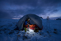 Female hike prepares breakfast at dawn from winter camp, Vestvågøy, Lofoten Islands, Norway