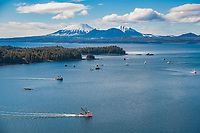 Commercial fishing vessels, Cape purse seiners position themselves in Sitka Sound, on the north side of Middle Island, for the first Herring Sac Roe fishery opener in 2006, southeast, Alaska. Mount Edgecumbe on the horizon.