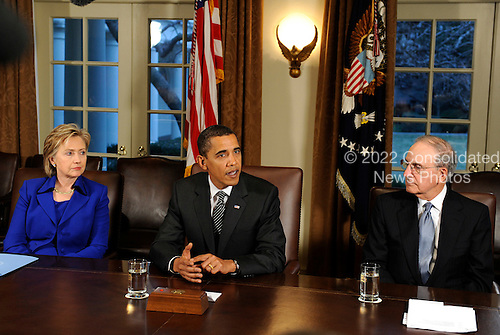 Washington, DC - January 26, 2009 -- United States President Barack Obama (C) speaks alongside Secretary of State Hillary Rodham Clinton (L) and former Senator George Mitchell's (Democrat of Maine) (R) as he delivers remarks about Mitchell's upcoming trip to Iraq in the White House in Washington on January 26, 2009. .Credit: Kevin Dietsch - Pool via CNP.