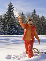 Deutschland, Frau mit Schlitten wirft Schneeball | Germany, woman with sledge throwing snowball