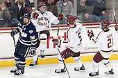 Greg Burke (UNH - 26) skates away as Pat Mullane (BC - 11), Michael Matheson (BC - 5) and Steven Whitney (BC - 21) celebrate. - The Boston College Eagles defeated the visiting University of New Hampshire Wildcats 5-2 on Friday, January 11, 2013, at Kelley Rink in Conte Forum in Chestnut Hill, Massachusetts.