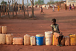 Evani Aman waits in a queue of jerry cans and buckets for her turn to obtain water in the Yida refugee camp in South Sudan. Some 53,000 refugees from Sudan's Nuba Mountains live in the camp, with an equal number living in two nearby camps.