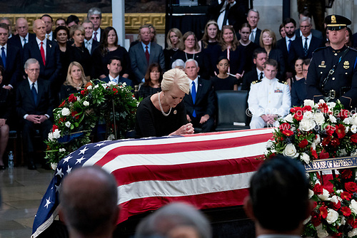 Cindy McCain, wife of, Sen. John McCain, R-Ariz., stands over her husband's casket as he lies in state in the Rotunda of the U.S. Capitol, Friday, Aug. 31, 2018, in Washington. (AP Photo/Andrew Harnik, Pool)