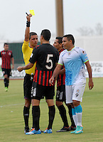 MONTERIA - COLOMBIA -04 -04-2015: Oscar Gomez, (Izq.) arbitro, muestra tarjeta amarilla a Luis Vergara (Cent.) jugador del Cucuta Deportivo, durante partido entre Jaguares FC y Cucuta Deportivo, por la fecha 13 de la Liga Aguila I-2015, jugado en el estadio Municipal de Monteria en la ciudad de Monteria.  / Oscar Gomez, (L) referee, shows yellow card to Luis Vergara (C) player of Cucuta Deportivo, during a match between Jaguares FC and Cucuta Deportivo for the  date 13 of the Liga Aguila I-2015 at the Municipal de Monteria Stadium in Monteria city, Photo: VizzorImage  / Jose Perdomo / Cont.