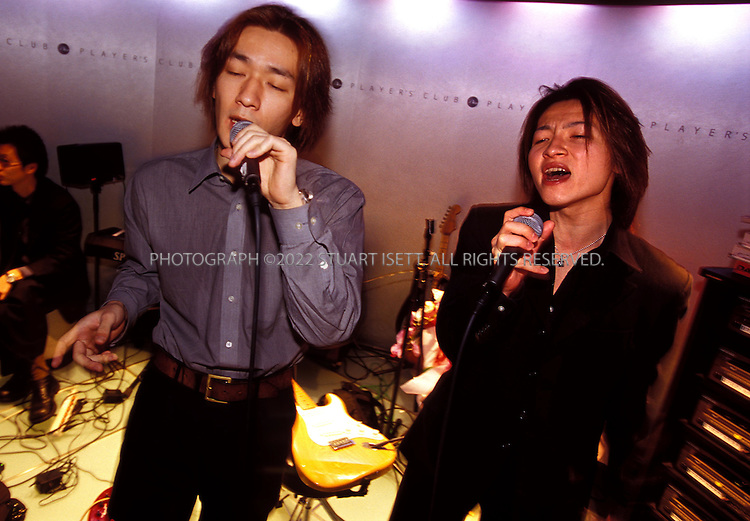 10/10/2002--Tokyo, Japan..At the Players Club, a chain of male hosts club, in Roppongi, Tokyo, male hosts sing karaoke for female clients...All photographs ©2003 Stuart Isett.All rights reserved.