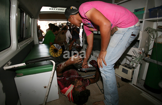 Palestinians carry a wounded boy into Al-Shifa hospital following Israeli air attacks, in Gaza City, Gaza Strip, 19 August 2011. Photo by Mahmud Nassar