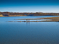 Fishermen trek onto a small finger of rocks normally covered by the waters of Hoover Reservoir. Water level on the lake is much lower than normal as crews work to complete a pollution mitigation project at the park's parking lots.