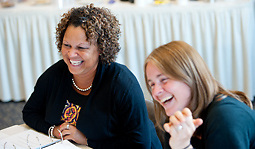 Tara Brooks, left, and Cat Cutcher, right, laugh during a simulation activity while participating in the Summer Institute of Diversity Education on July 11, 2012 in Athens, Ohio.