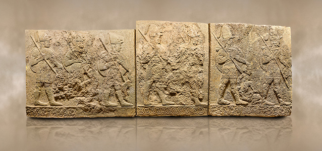 Photo of Hittite sculpted orthostats panels of Long Wall Limestone, Karkamıs, (Kargamıs), Carchemish (Karkemish), 900-700 B.C. Soldiers. Anatolian Civilisations Museum, Ankara, Turkey<br /> <br /> Figures of helmeted warriors. They have their shield in their back and their spear in their hand. The prisoner in their front is depicted as small. The lower part of the orthostat is decorated with braiding motifs. <br /> <br /> On a brown art background.