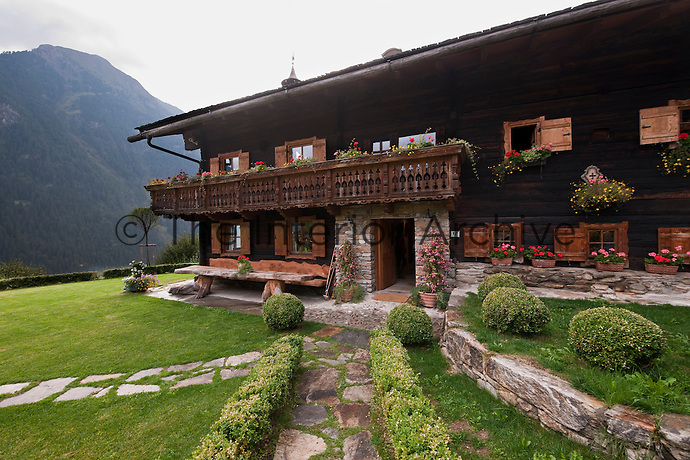 The entrance to a typical mountain chalet with a stone and wood-clad facade decorated with flowers in window boxes