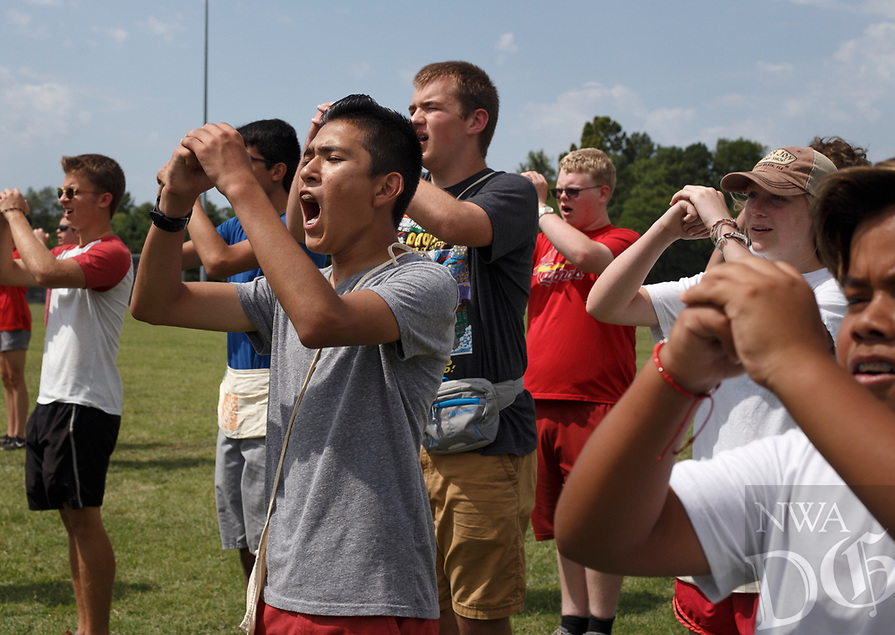 NWA Democrat-Gazette/CHARLIE KAIJO Sophomore Osvaldo Duran (left) joins marching band members in a end of practice chant, Monday, August 6, 2018 at Rogers High School in Rogers. <br />