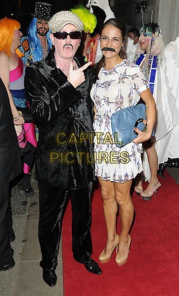 CHRIS EVANS & NATASHA SHISHMANIAN.Freddie For A Day charity gala arrivals, Savoy hotel, the Strand, London, England..September 5th, 2011.full length black suit velvet grey gray flat cap hat sunglasses shades hand pointing finger up married husband wife dress moustache mustache facial hair blue clutch bag funny.CAP/CAN.©Can Nguyen/Capital Pictures.