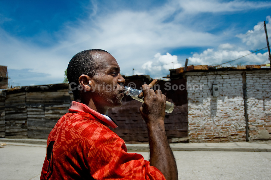 A Cuban man drinks from a bottle of cheap rum and smokes a cigar on the street of Santiago de Cuba, Cuba, 3 August 2008. About 50 years after the national rebellion, led by Fidel Castro, and adopting the communist ideology shortly after the victory, the Caribbean island of Cuba is the only country in Americas having the communist political system. Although the Cuban state-controlled economy has never been developed enough to allow Cubans living in social conditions similar to the US or to Europe, mostly middle-age and older Cubans still support the Castro Brothers' regime and the idea of the Cuban Revolution. Since the 1990s Cuba struggles with chronic economic crisis and mainly young Cubans call for the economic changes.