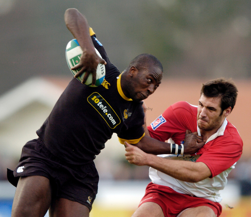 Photo: Richard Lane..Biarritz Olympique v London Wasps. Heineken Cup. 15/01/2005..Ayoola Erinle is tackled by Thibault Lacroix.