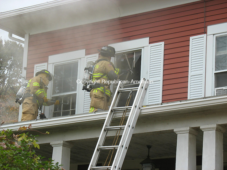 ROXBURY, CT - 22 October 2010 - 102210RH03 - Firefighters work to douse and ventilate a smouldering fire at 339 Painter Hill Road in Roxbury. Nobody was home at the time. Rick Harrison Republican-American