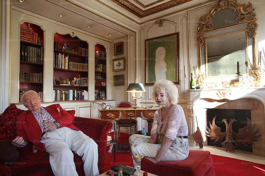 Wolf C Hartwig aged 91, producer of epic films and soft-porn features, with his fourth wife, and actress, Veronique Vendell in their apartment on Avenue de Foch, Paris. Wolf Hartwig was awarded a Bambi Award from German Cinema for his film 'The Iron Cross' which was directed by Sam Peckinpah starring James Coburn with Veronique Vendell. A producer working in exploitation genres, soft porn, sex, lurid, violent and sensational features. Other films he produced include 'Horrors from Spider Island'. 'Lady Hamilton' and 'Virgin of the Seven Seas'.//Wolf Hartwig and his wife Veronique Vendell sitting in their salon living room drinking champagne