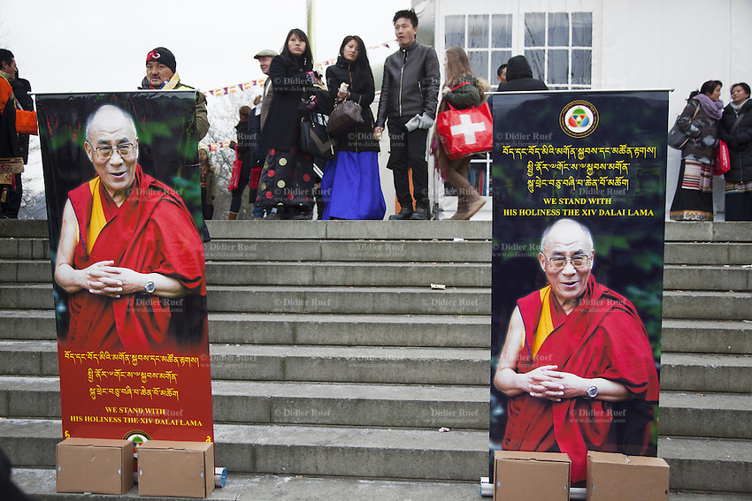 """Switzerland. Basel. St. Jakobshalle. A group of men and women, all tibetan, and a poster of His Holiness the Dalai Lama. The 14th and current Dalai Lama is Tenzin Gyatso, recognized since 1950. He is the current Dalai Lama, as well as the longest-lived incumbent, well known for his lifelong advocacy for Tibetans inside and outside Tibet. Dalai Lamas are amongst the head monks of the Gelug school, the newest of the schools of Tibetan Buddhism. The Dalai Lama, also called """" Ocean of Wisdom"""" is considered as the incarnation of Chenresi, the Bodhisattva of compassion who is also the protective deity of Tibet. The flag of Switzerland consists of a red flag with a white cross (a bold, equilateral cross) in the centre. 7.02.2015 © 2015 Didier Ruef"""