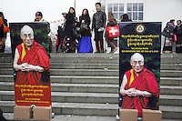 "Switzerland. Basel. St. Jakobshalle. A group of men and women, all tibetan, and a poster of His Holiness the Dalai Lama. The 14th and current Dalai Lama is Tenzin Gyatso, recognized since 1950. He is the current Dalai Lama, as well as the longest-lived incumbent, well known for his lifelong advocacy for Tibetans inside and outside Tibet. Dalai Lamas are amongst the head monks of the Gelug school, the newest of the schools of Tibetan Buddhism. The Dalai Lama, also called "" Ocean of Wisdom"" is considered as the incarnation of Chenresi, the Bodhisattva of compassion who is also the protective deity of Tibet. The flag of Switzerland consists of a red flag with a white cross (a bold, equilateral cross) in the centre. 7.02.2015 © 2015 Didier Ruef"