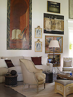 In the living room antique and contemporary paintings and furniture exist comfortably side-by-side