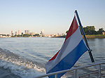 Dutch national flag flying at the back of a boat with buildings of Rotterdam, Netherlands in the background.