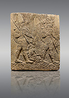 Picture & image of Hittite sculpted Orthostats panel of Long Wall Limestone, Karkamıs, (Kargamıs), Carchemish (Karkemish), 900-700 B.C. Soldiers. Anatolian Civilisations Museum, Ankara, Turkey<br /> <br /> Figure of two helmeted warriors. They have their shield in their back and their spear in their hand. The prisoner in their front is depicted small. A human head is depicted in the left hand of the warrior in the front. The warrior at the rear holds the prisoners sitting on his lap from his hair. Below this figure, which was described small, lies yet another small human figure. <br /> <br /> On a gray background.