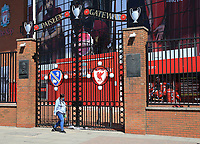May 4th 2020, Liverpool, United Kingdom;  Anfield stadium during the suspension of the Premier League due to the Covid-19 virus pandemic;  a woman  wearing a face mask walks past the locked Paisley Gateway entrance to the Kop