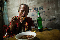 "An elderly man who asked not to be named eats fried noodles with peanuts and spices at a small unnamed outdoor noodle cafe at the bottom of Shibati, or 18 Steps, in central Chongqing. He called the dish dou gan. The man says he eats at the restaurant almost every night because he likes the flavors of the dishes so much.<br /> <br /> The cook, Tong Su Chun, has been cooking at the spot, which is run by his nephew, for about 20 years. The neighborhood is slated for redevelopment, and all residents, including this shop, must leave the area by October 2014. Tong Su Chun said he didn't know what he would do after the restaurant closes. ""I'll take a break,"" he said, ""and then find something new."" The restaurant typically serves a couple hundred people in a night, most spending about 15 RMB."