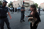 A Secular girl with her dog pass by the thousands of Ultra-Orthodox Jews who continued their protest against the opening of a parking lot on the Shabbat day of rest, Jerusalem, Saturday, June 27, 2009. Approximately 40 ultra-Orthodox demonstrators were arrested and six people were wounded during the riots. Photo By : Tess Scheflan / JINI