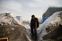 A man walks through a demolition site in the Uighur section of Urumqi, Xinjiang, China.