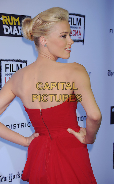 "Amber Heard.arriving at the Los Angeles Premiere of ""The Rum Diary"" at LACMA in Los Angeles, California, USA, .October 13th 2011. .half length red dress strapless back over shoulder hair up bun profile  hands on his rear behind .CAP/ROT/TM.©TM/Roth Stock/Capital Pictures"