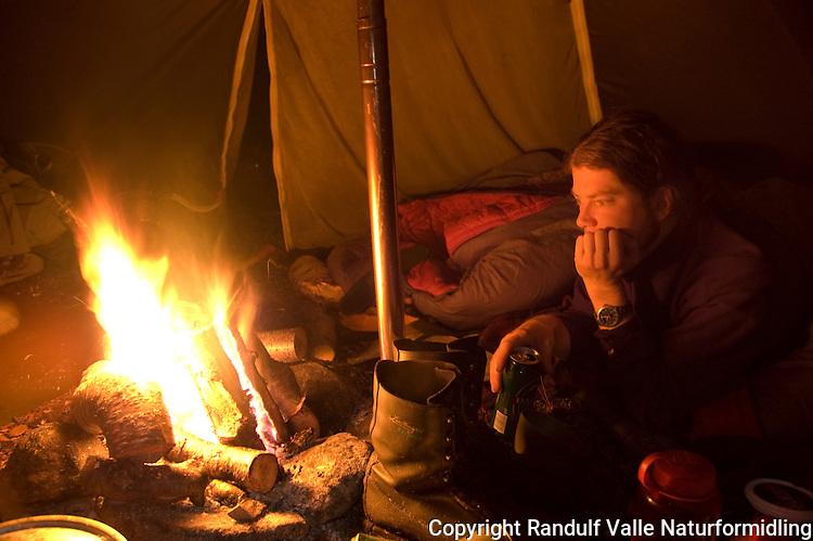 Mann foran bål i mørk lavvo ---- Man in front of camp fire inside tent