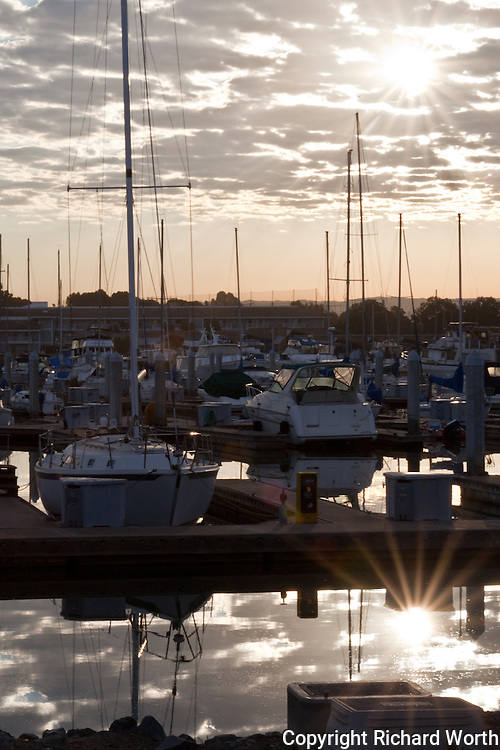 The morning sun creates a sun burst in the sky and another with its reflection in the water at San Leandro Marina on San Francisco Bay.