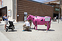 Woman takes picture of her husband, father and sons in front of a pink cow at Expo 2015, Rho-Pero, Milan, June 2015. Next to the cow there is a sign that invite to make selfie with it. &copy; Carlo Cerchioli<br /> <br /> Una donna fa una fotografia a suo marito con i figli e suo padre di fronte ad una mucca rosa a Expo 2015, Rho-Pero, Milano, giugno 2015. Vicino alla mucca un cartello invita a farsi dei selfie con la mucca.