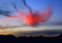 A setting sun provides color to wispy clouds along the Pacific Ocean in Baja California, Mexico
