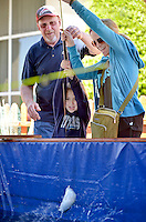 NWA Democrat-Gazette/BEN GOFF -- 04/26/15 Campbell Sullivan, 5, of Springdale gets help from her mother Jenna Sullivan and Dick Lawton with FLW as she reels in a fish in the FLW Trout Pond booth at the FLW Expo at the John Q. Hammons Center in Rogers on Sunday Apr. 26, 2015.