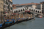 Gondolas and crowds of tourists looking on to the Grand Canal from the Rialto bridge. Venice, Italy.