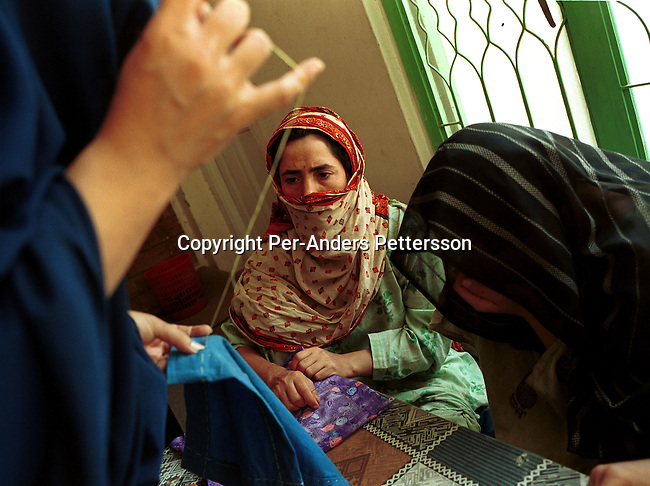 Afghan refugee women at the Center for Street Children and Women on September 25, 2001 in Peshawar Pakistan. They attend daily broidery classes to learn skills . They have to wear a traditional Burqa dress while walking in the streets. About 1 million Afghan refugees are in Pakistan, mainly in Peshawar. .Photo Per-Anders Pettersson/ Grazia Neri