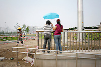 """CHINA. Beijing. Tourists trying to catch a glimpse of the new Olympic park. In recent years construction has boomed in Beijing as a result of the country's widespread economic growth and the awarding of the 2008 Summer Olympics to the city. For Beijing's residents however, it seems as their city is continually under construction with old neighborhoods regularly being razed and new apartments, office blocks and sports venues appearing in their place. A new Beijing has been promised to the people to act as a showcase to the world for the 'new' China. Beijing's residents have been waiting for this promised change for years and are still waiting, asking the question """"Where's the new Beijing?!"""". 2008."""