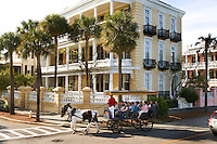 A group of tourists take a horse and carriage sightseeing tour in Charleston, SC.