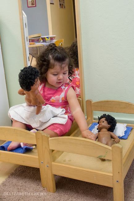 Berkeley CA Mexican girl, one and a half, imagining that she and dolls are equals while sharing beds at Children's Creative Play Space MR