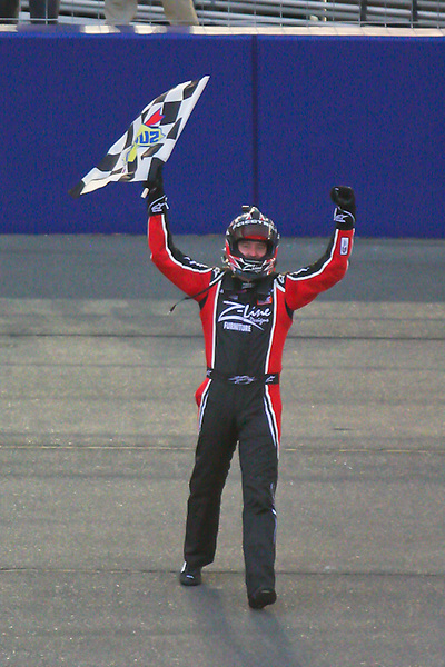 Feb. 20, 2010, Auto Club Speedway, CA: Kyle Busch celebrates his victory as usual with the checkered flag.