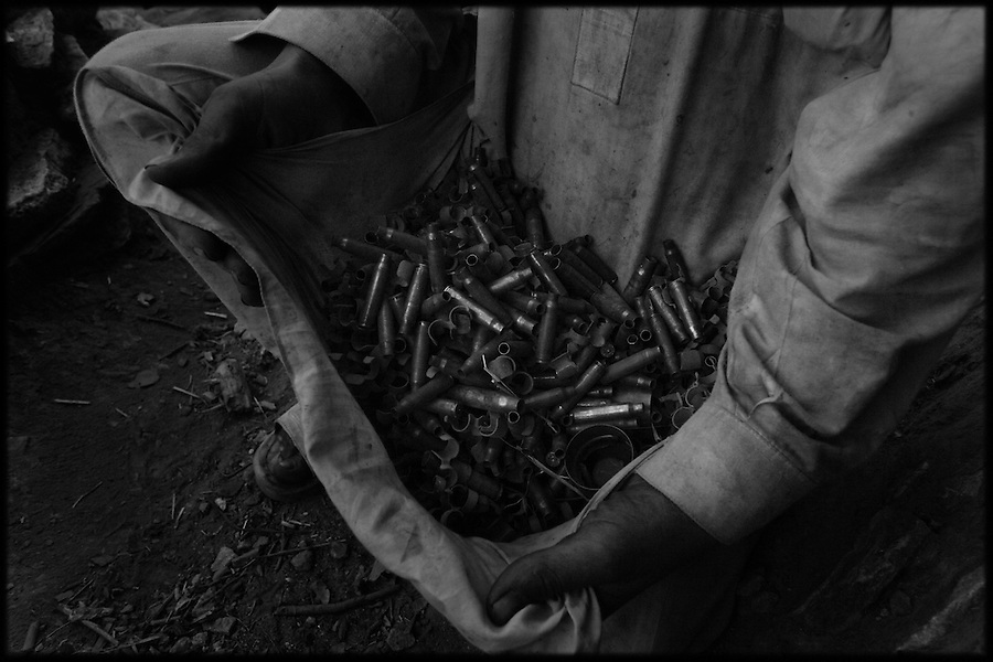 After a short sharp firefight, a teen-aged Afghan displays the brass and links he has collected from around the feet of soldiers from Baker Co. 2-12 Infantry Regiment 4th Brigade 4th Infantry Division in Afghanistan's Korengal Valley in the summer of 2009.