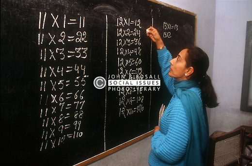 Female teacher writing arithmetic tables on the blackboard in senior secondary modern school; Punjabi University; Patiala; Punjab; India,