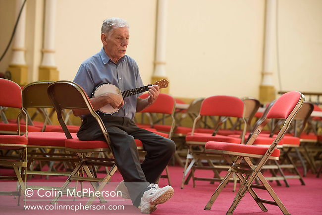 A fan attending the George Formby Appreciation Society's annual gathering in Blackpool, practicing on his ukulele prior to playing to the audience at the town's Winter Gardens. The society was formed in 1961 and holds an annual event to celebrate the life of the famous Lancastrian singer and entertainer.