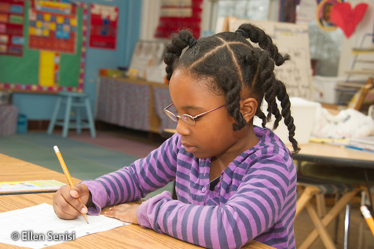 MR / Schenectady, New York. Yates Arts-in-Education Magnet School (urban public school). First grade classroom. Student (girl, 6, African American) uses pencil to work on worksheet. MR: Wil40. ID: AM-g1w. © Ellen B. Senisi.