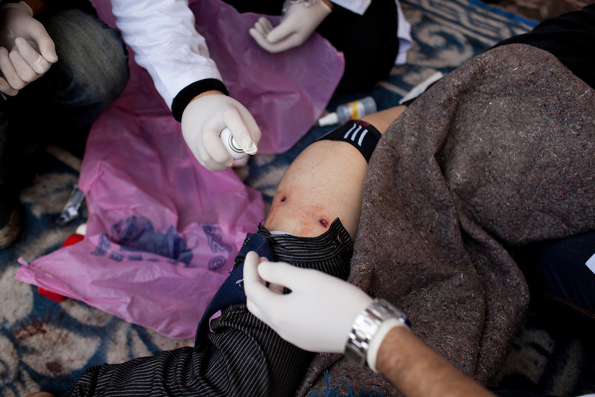 An injured Egyptian protester is treated by doctors in a triage unit during protests near central Cairo's Tahrir Square, November 20, 2011. Doctors claim the injury was a result of the use of live rounds by Egyptian security forces.  Photo: Ed Giles