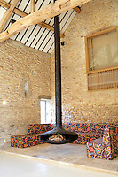 The wood burning stove is a French design and has been placed for maximum effect in the centre of the massive Art Barn where its long flue soars into the rafters high above; the modular sofa is covered in a vintage 1920's print